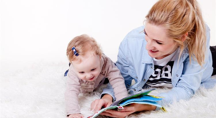 Nursery assistant reading book with baby