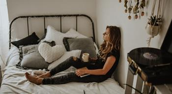 Woman sitting on bed with cup of tea