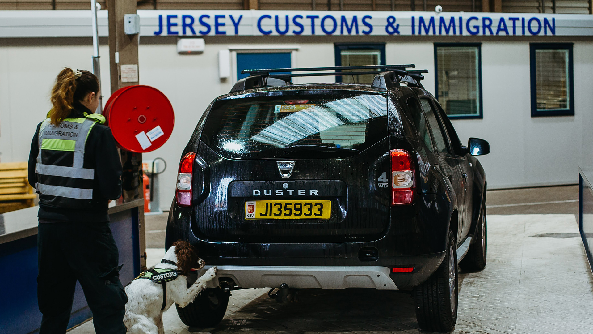 Photo of vehicle being checked by customs officer and dog