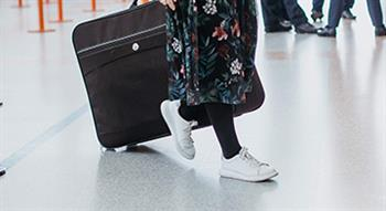 Photo of women wheeling suitcase in airport departures