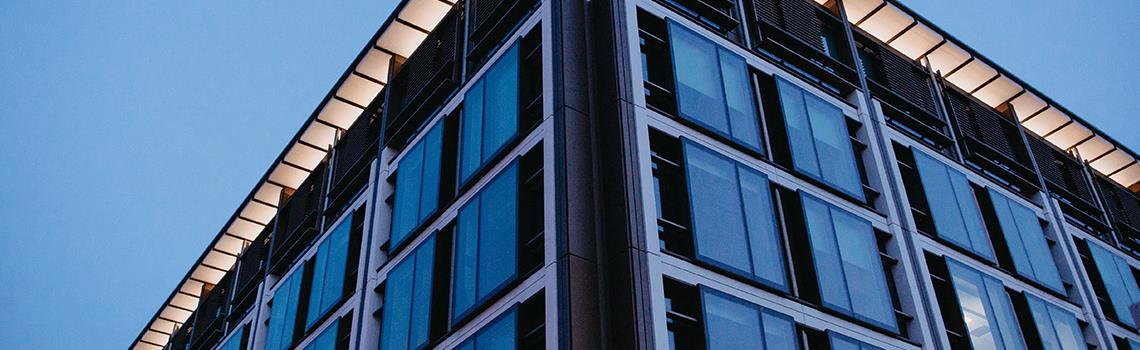 Photo of corner of building with ights on shot at dusk in blue light