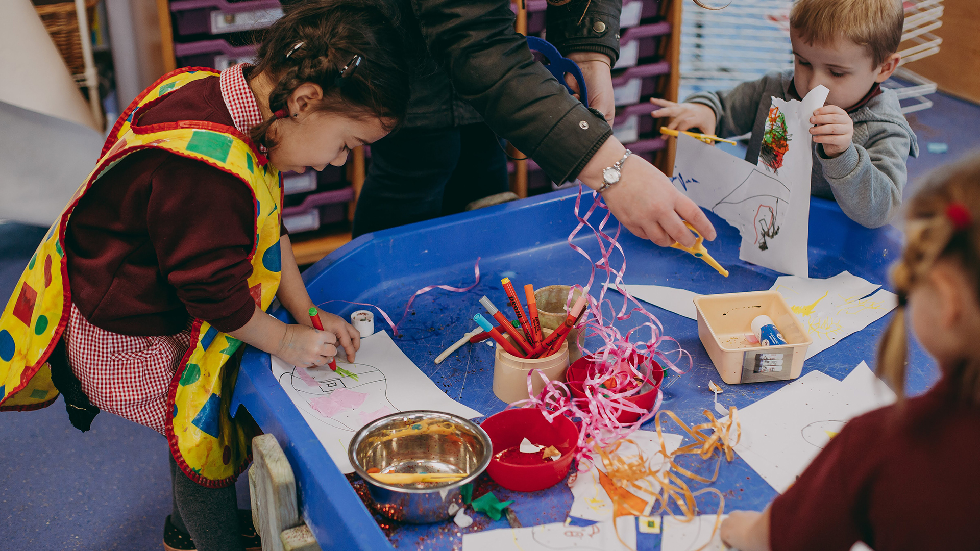 Photo of children colouring at table
