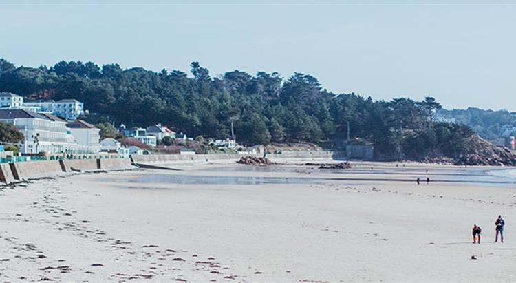 Photo of St brelades bay, long sandy beach, people walking on beach at low tide