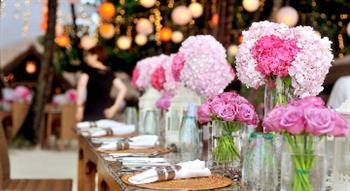 Photo of row of pink and white flowers in vases at a laid table
