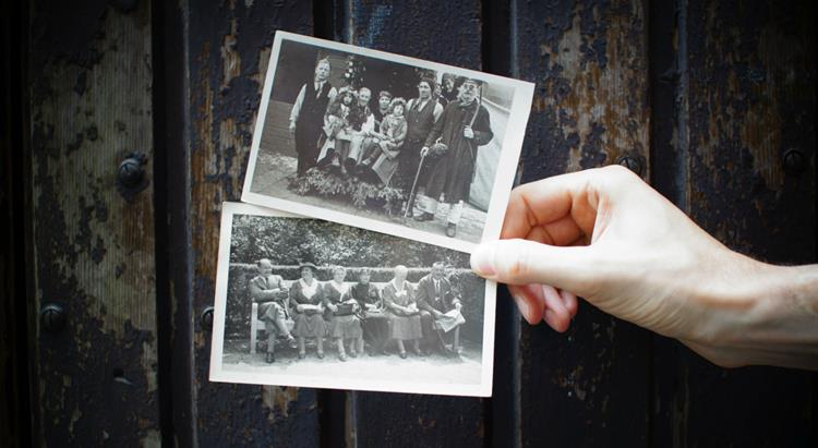 a hand holds up two old family photographs