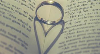 Wedding ring in page fold creating heart shape from shadow