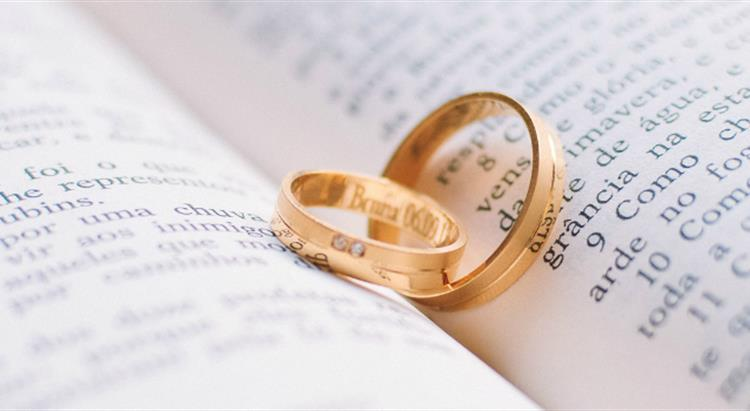 Photo of gold wedding ring placed on open book