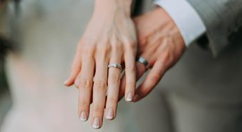 Photo of hands holding with wedding rings on