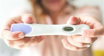 Woman holding positive pregnancy test